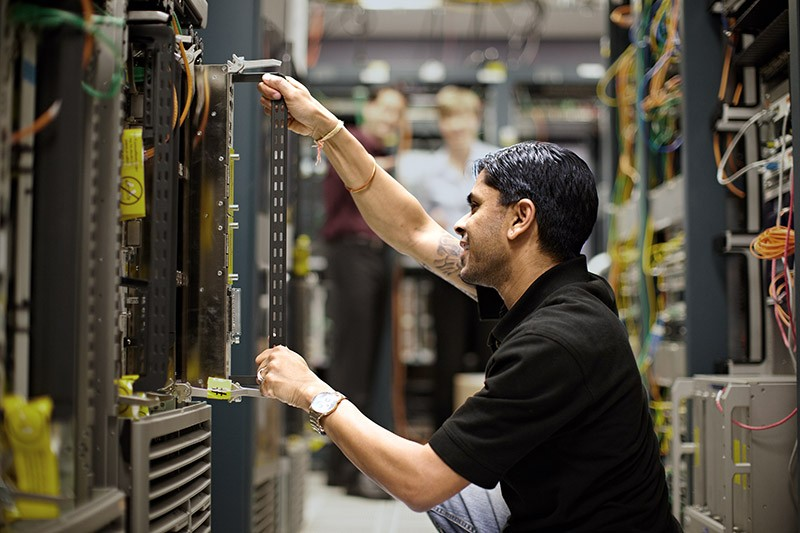 IT admin installing rack mountable server in data center