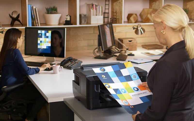 Business woman in office grabbing print design from printer