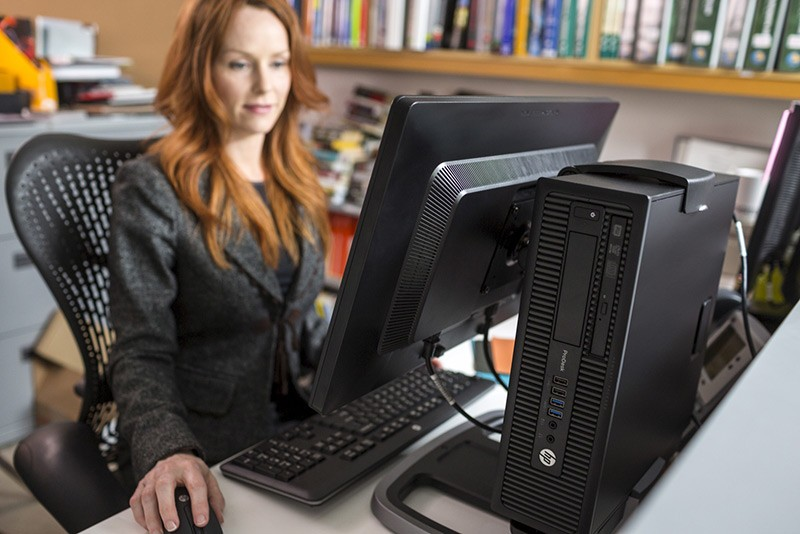 HP-business-woman-using-ProDesk-600-SFF-mounted-to-the-back-of-HP-ProDispaly-P221-HP20130924146