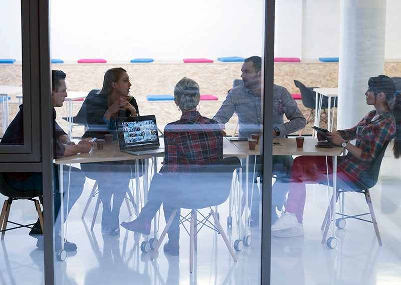 Business team having a brainstorming session, while working on laptop and tablet computers
