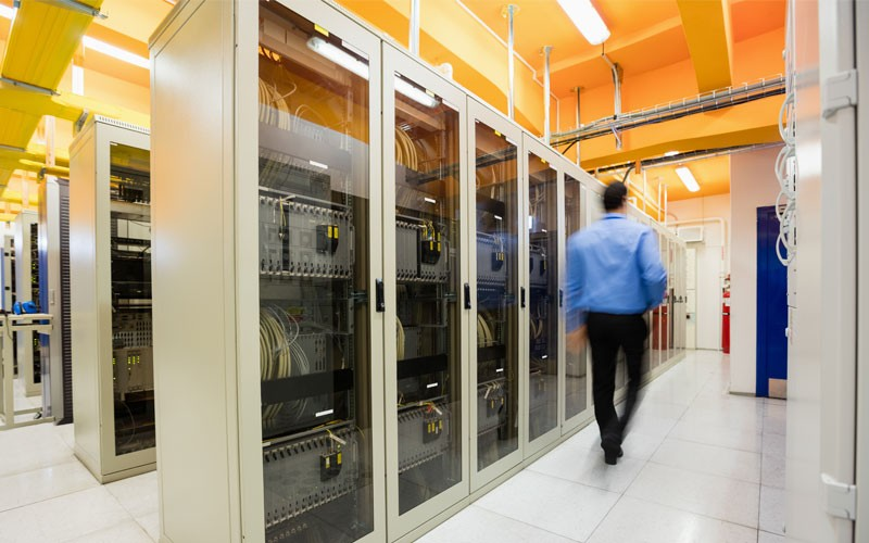 IT technician walking through server room