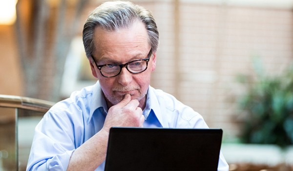Executive reviewing payment models off of his laptop computer