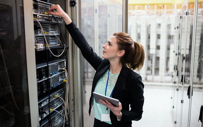 IT professional reaches for cable in data center with tablet in hand