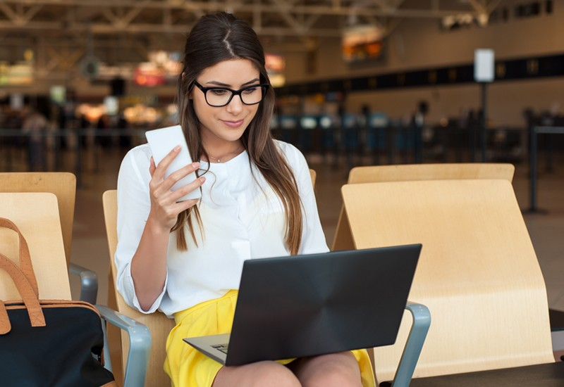 Business woman on phone and laptop in airport